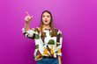 canvas print picture - young pretty woman feeling shocked and surprised, pointing and looking upwards in awe with amazed, open-mouthed look against purple background