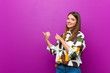 canvas print picture - young pretty woman smiling cheerfully and casually pointing to copy space on the side, feeling happy and satisfied against purple background