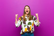canvas print picture - young pretty woman shouting aggressively with an angry expression or with fists clenched celebrating success against purple background