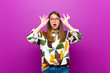 canvas print picture - young pretty woman feeling shocked, amazed and surprised, holding glasses with astonished, disbelieving look against purple background