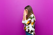 canvas print picture - young pretty woman covering eyes with hands with a sad, frustrated look of despair, crying, side view against purple background
