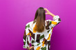 canvas print picture - young pretty woman feeling clueless and confused, thinking a solution, with hand on hip and other on head, rear view against purple background