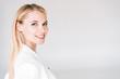Leinwandbild Motiv smiling beautiful young blonde woman isolated on grey
