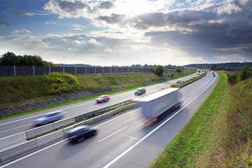 highway in the country with driving cars and trucks in motion blur under a dramatic sky with clouds, concept for traffic, transport and the environment, copy space