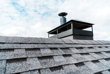 Selective Focus Of Modern Chimney On Rooftop Of House