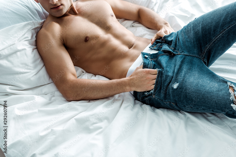 Fototapeta cropped view of shirtless man taking off blue jeans while lying on bed