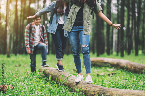 Fotografia Group of traveler walking on the log while hiking in the forest
