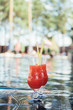 two glasses with tasty, natural fruit beverage at poolside