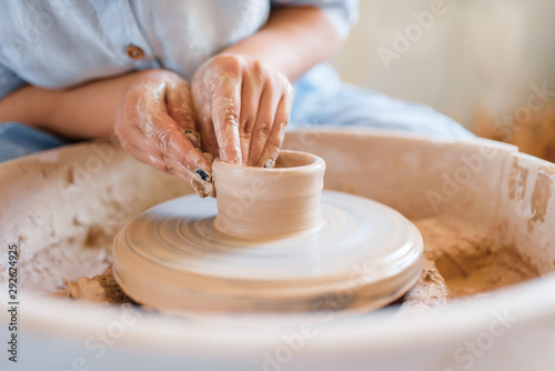 Fotomural  Female potter making a pot on pottery wheel
