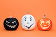 canvas print picture - Three cute Halloween Pumpkins side by side over orange background. Halloween background.