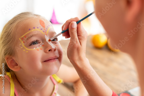 Cuadros en Lienzo Young mother painting daughters face for Halloween party
