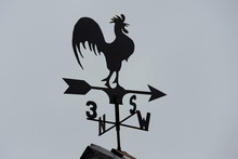 Weather Vane In The Form Of A Rooster On The Roof Of The House