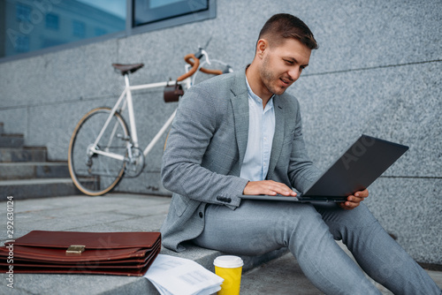 Businessman with bike and laptop having lunch Canvas Print