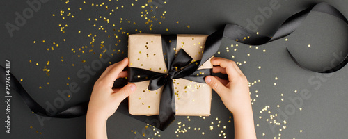 Christmas present stylish gift boxe in kids hands on black background Wallpaper Mural