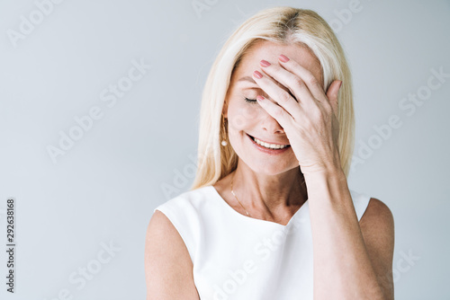 happy blonde mature woman with closed eyes isolated on grey Canvas Print