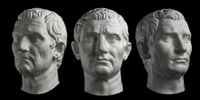 Three Gypsum Copy Of Ancient Statue Head Of Guy Julius Caesar Isolated On Black Background. Plaster Sculpture Man Face.