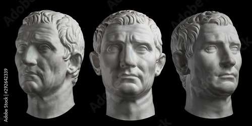 Fotomural  Three gypsum copy of ancient statue head of Guy Julius Caesar isolated on black background