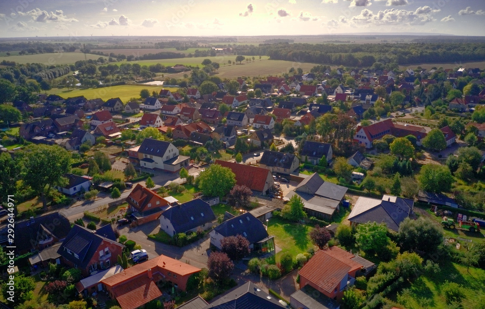 Fototapeta Oblique aerial view of a village in Germany with detached houses, yarns, lawns and roads