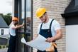 Leinwanddruck Bild - selective focus of cheerful builder looking at blueprint near coworker