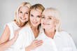 cheerful three generation blonde women isolated on grey