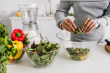 cropped view of woman preparing salad in kitchen