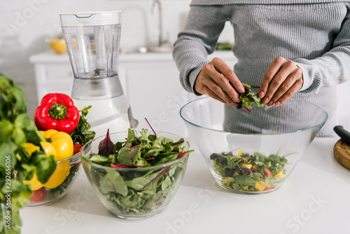 cropped view of woman preparing salad in kitchen - 292656106