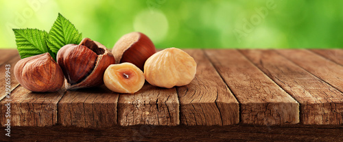 Nuts on wooden table and nature in background