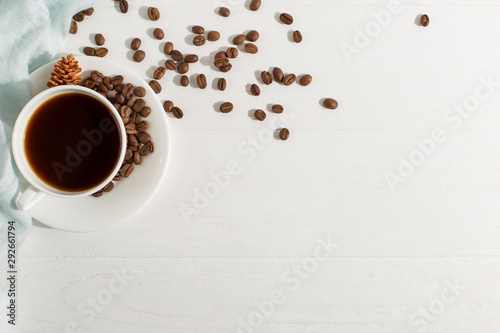 Blue scarf, coffee grains and a cup on a white table, morning start day. Autumn mood background, copy space, flat lay.