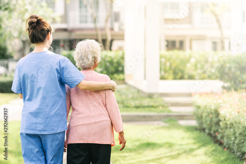 nurse caregiver support walking with elderly woman outdoor Canvas