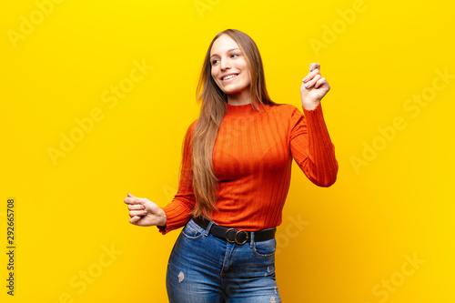 young pretty woman smiling, feeling carefree, relaxed and happy, dancing and listening to music, having fun at a party against orange background - 292665708