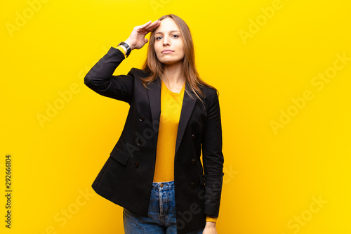 young pretty businesswoman greeting the camera with a military salute in an a...