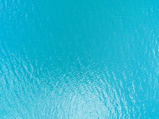Fototapeta na wymiar Aerial view of a Crystal clear sea water texture. View from above Natural blue background. Turquoise ripple water reflection in tropical beach. Blue ocean wave. Summer sea. Drone. Top view