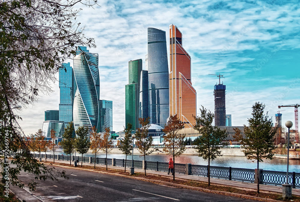 Fototapeta Panorama of high buildings with river  reflections under cloudy autumn sky in Moscow