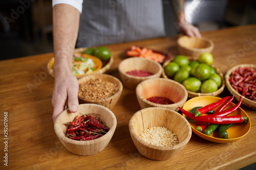 Background image of unrecognizable chef setting ingredients on wooden table whil Fototapet