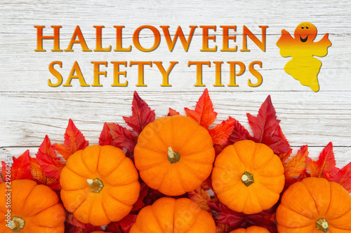 Halloween Safety Tips message with red and orange fall leaves and a pumpkins on weathered wood