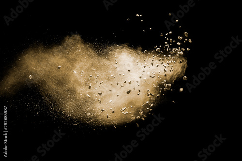 Fotografie, Obraz Split debris of brown stone exploding with brown powder against black background