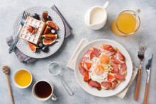 Dishes For Home Cooked Hearty Breakfast. Fried Eggs With Sausages And Tomatoes. Belgian Fluted Waffles With Figs And Grapes. Gray Concrete Background