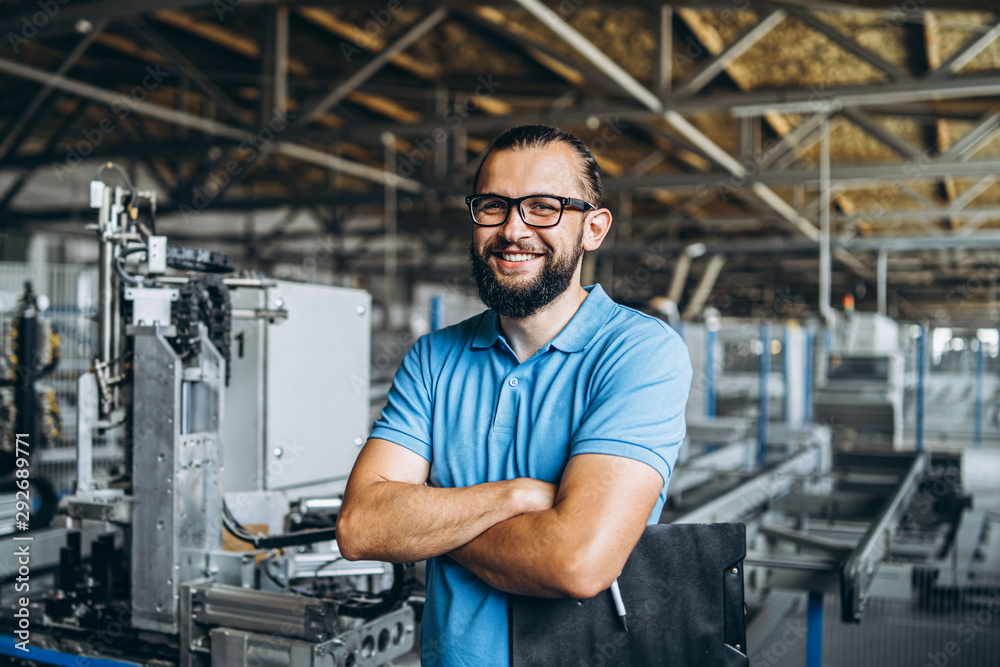 Fototapety, obrazy: Young engeneer manager with beard checking manufactory, workplace and machinery in big factory.