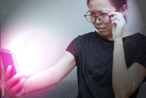 Fotomural Asian female trying to read something in her mobile phone with red spot on her hand