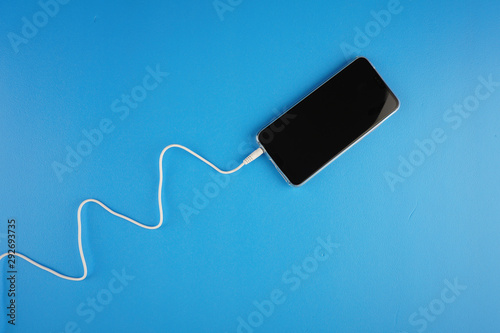Wave shape of white cable attached on smartphone over blue background Canvas Print