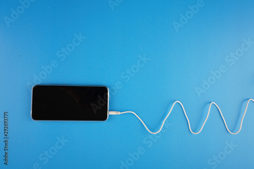 Photo Wave shape of white cable attached on smartphone over blue background