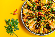 Pan With Spanish Paella With Seafood On A Yellow Background, Top View