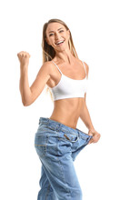 Happy Young Woman In Loose Jeans On White Background. Weight Loss Concept