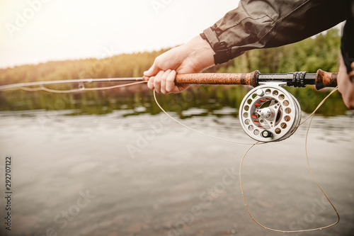 Canvas-taulu Fisherman spool of rope using rod fly fishing in river