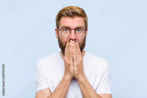 young blonde adult man feeling worried, upset and scared, covering mouth with ha Wallpaper Mural