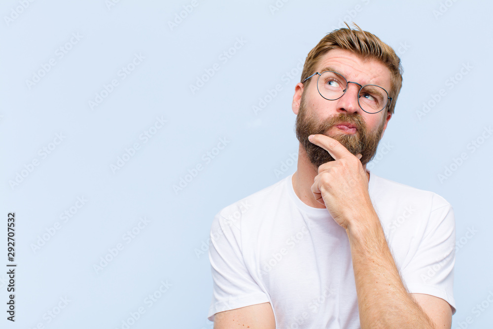 Fototapeta young blonde adult man thinking, feeling doubtful and confused, with different options, wondering which decision to make