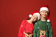 Cute Children In Christmas Sweaters And Santa Hats On Color Background