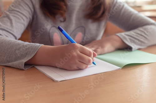 Canvas hand of a teenage girl writes with a ballpoint pen in a terad during a lesson at