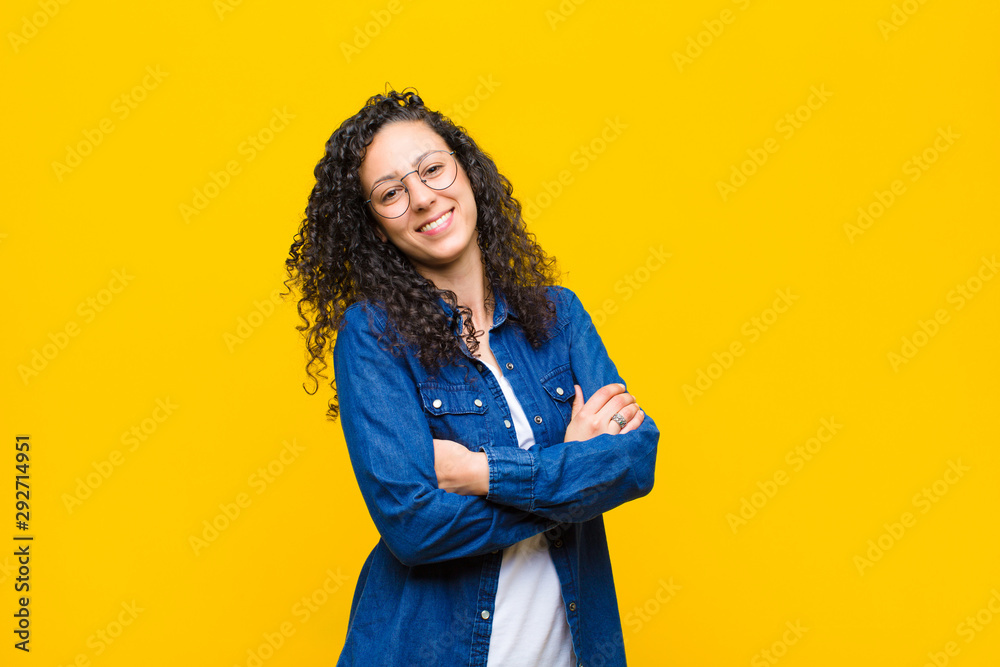 Fototapety, obrazy: young pretty woman laughing happily with arms crossed, with a relaxed, positive and satisfied pose against orange wall