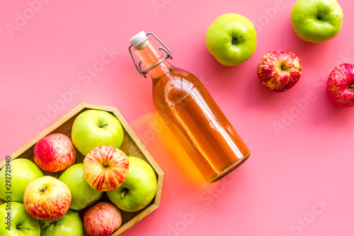 Fotografia Apple cider in bottle near tray with fruits on pink background top view copy spa